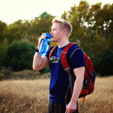 Drinking from Lunatec Hydration Spray Bottle.